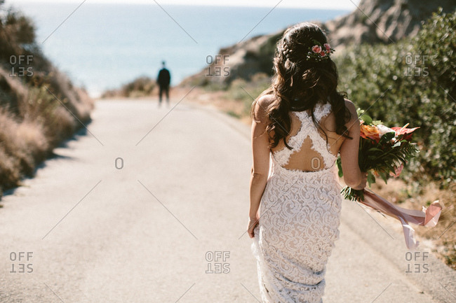 Bride walking down the road to her groom