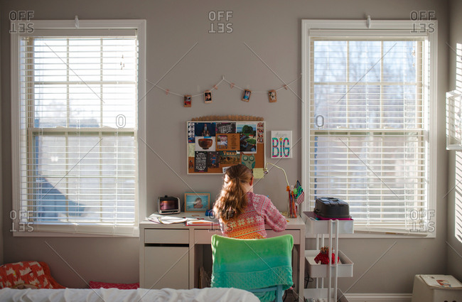 Girl working at desk between two windows