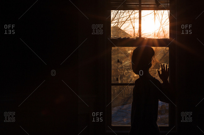 Silhouette of a girl with hand on a window