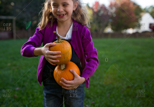 Girl stacking two pumpkins