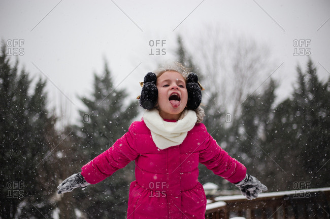Girl in pink coat catching snow on tongue