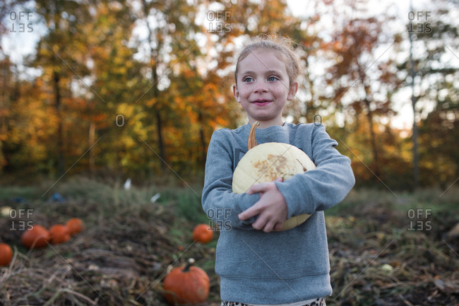Girl holding a white pumpkin in patch