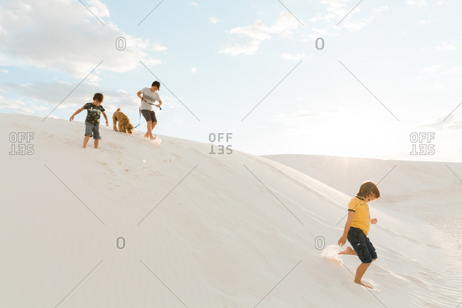 Three siblings and dog playing on hills at White Sands National Monument