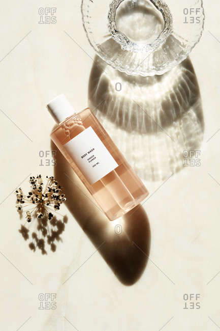 Liquid body wash beside glass dish