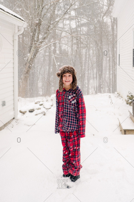 Boy in the snow in pajamas and furry hat