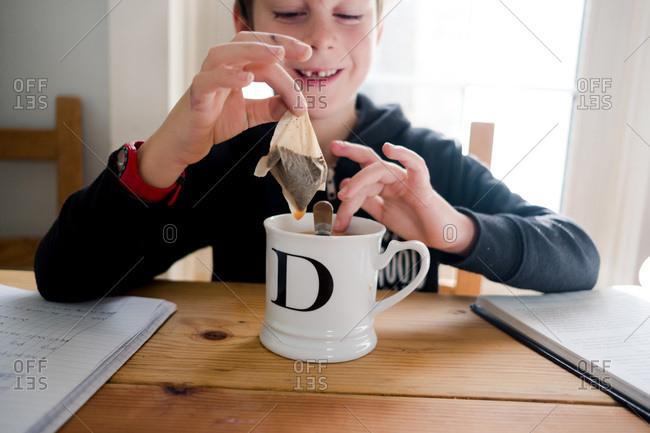 Young boy preparing tea while doing homework