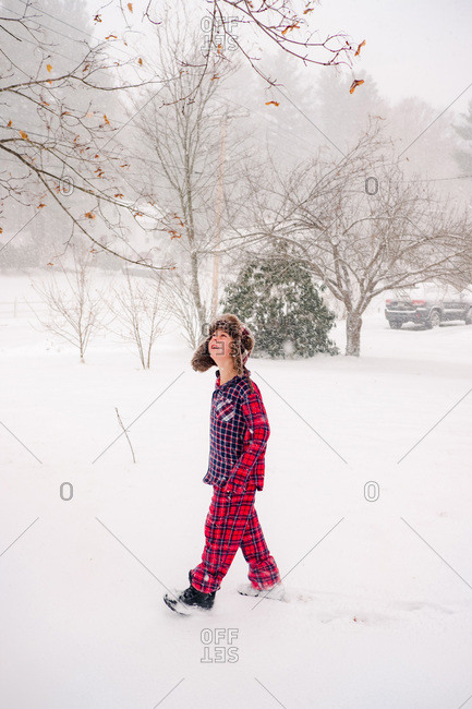 Boy walking in the snow in pajamas and furry hat