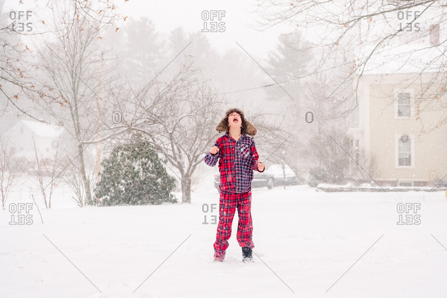 Young boy catching snowflakes in the snow in pajamas and furry hat