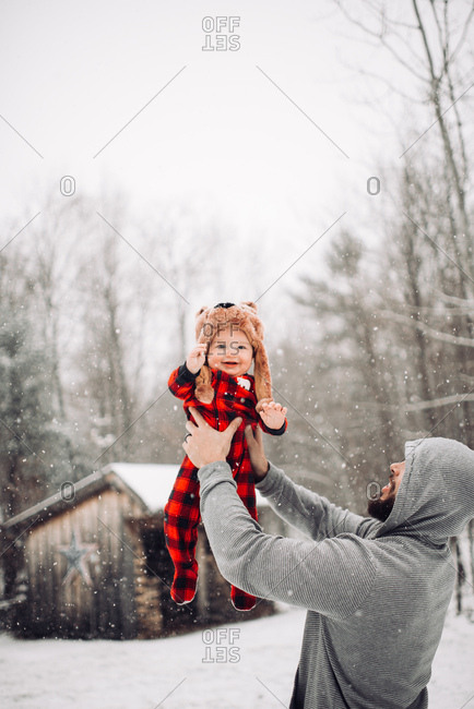 Man holding baby up in the air during snowfall