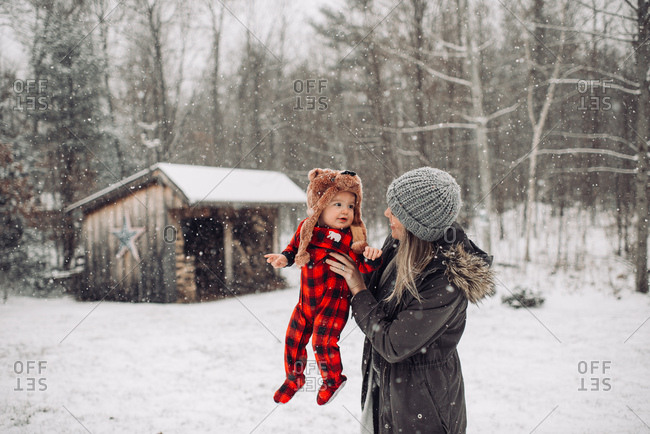 Woman holding baby outdoors during snowfall