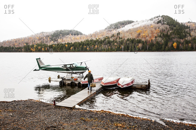 Ashland, Maine - October 26, 2016: Pilot walking towards floatplane on shoreside dock
