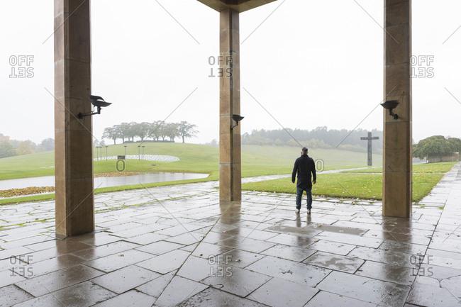 Smogen, Sweden - October 9, 2014: Rear view of man under shelter during rain