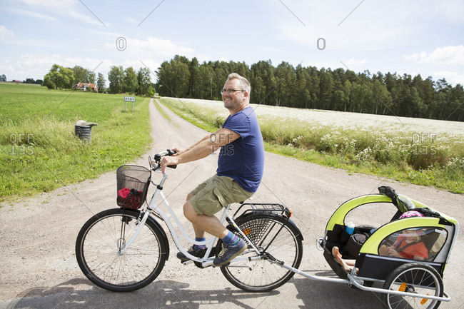 Man cycling with his daughter in Smaland, Sweden