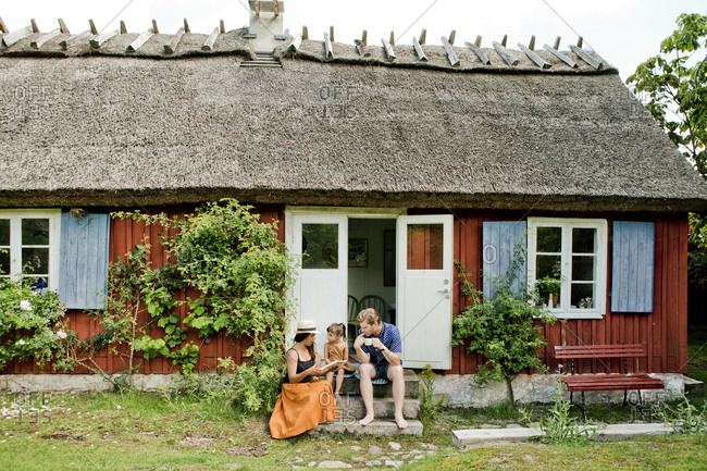 Family sitting on steps in Friseboda, Sweden