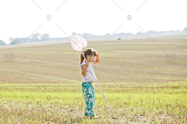 Girl with bug net in field in Friseboda, Sweden