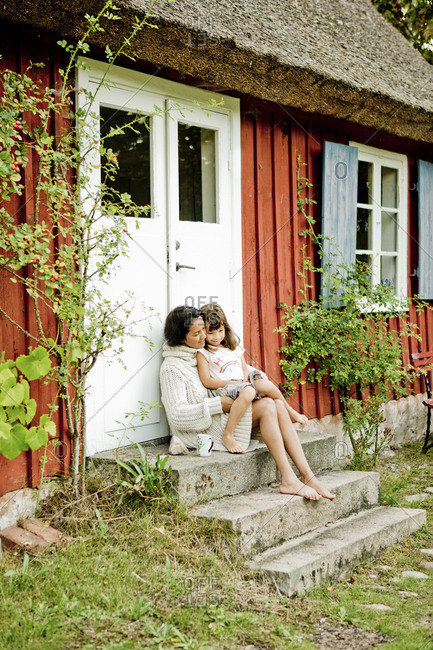 Mother and daughter sitting on steps in Friseboda, Sweden