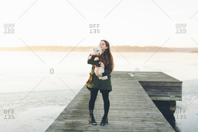 Young woman on pier with her dog during winter in Blekinge, Sweden