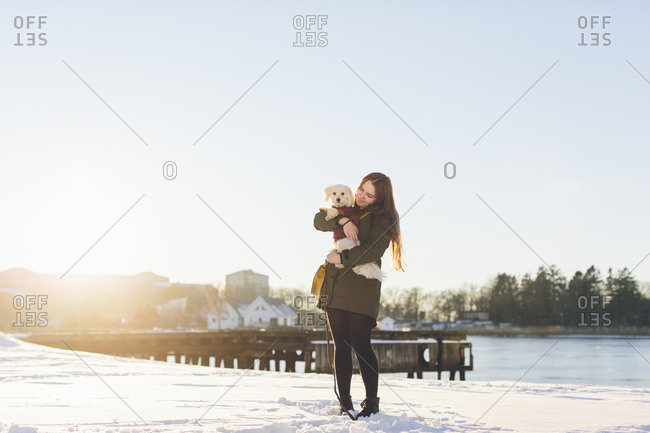 Young woman with her dog during winter in Blekinge, Sweden