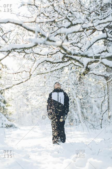 Boy walking in forest during winter in Blekinge, Sweden