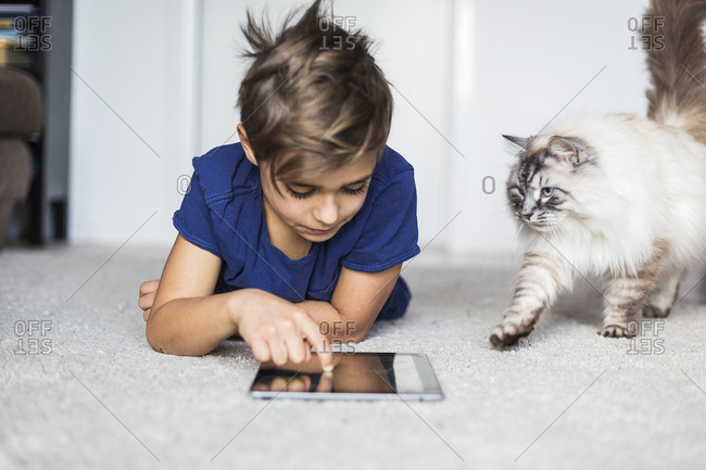 Boy lying on floor with tablet PC