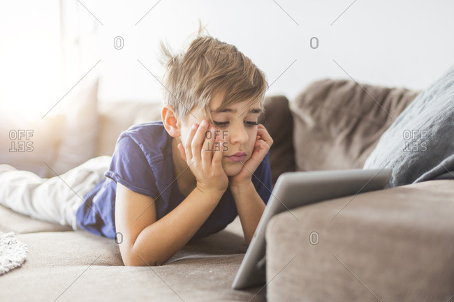 Boy on sofa playing with tablet PC