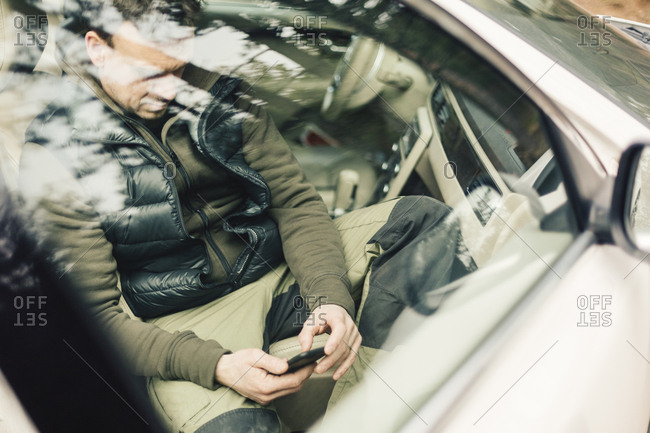 Man on smart phone behind car window in Sweden