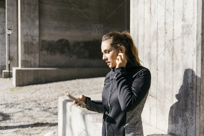 Young woman with smart phone on street in Stockholm, Sweden