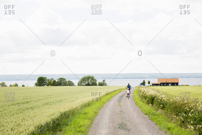 Family cycling along rural road in Smaland, Sweden