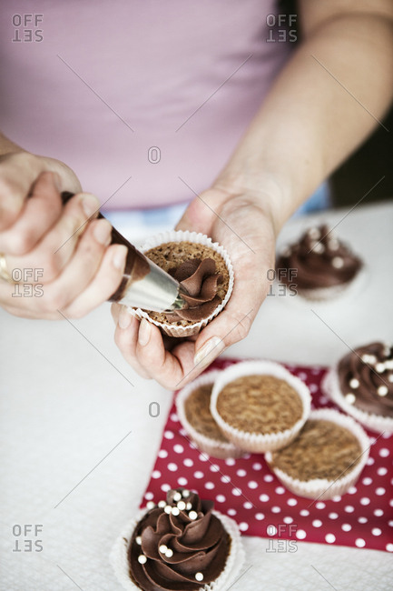 Hands of woman icing cupcakes in Sweden