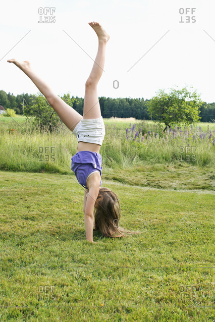 Girl doing cartwheel in Kallandso, Sweden