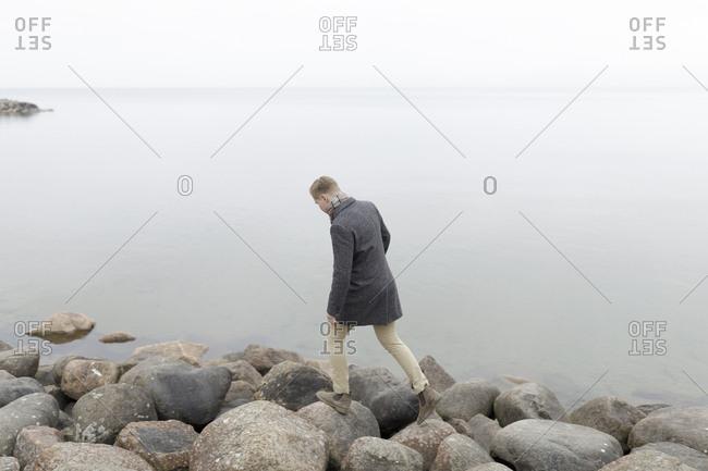Man on rocky coastline in Smaland, Sweden