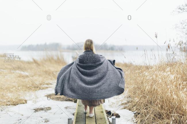 Woman wearing blanket during winter in Blekinge, Sweden