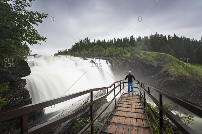 Man at lookout of waterfall in Jamtland, Sweden