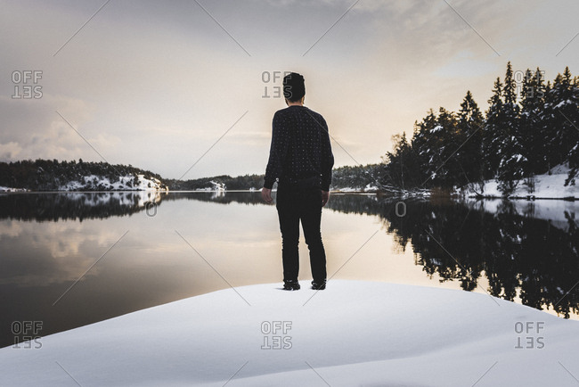 Rear view of man by lake in snow in Sodermanland, Sweden