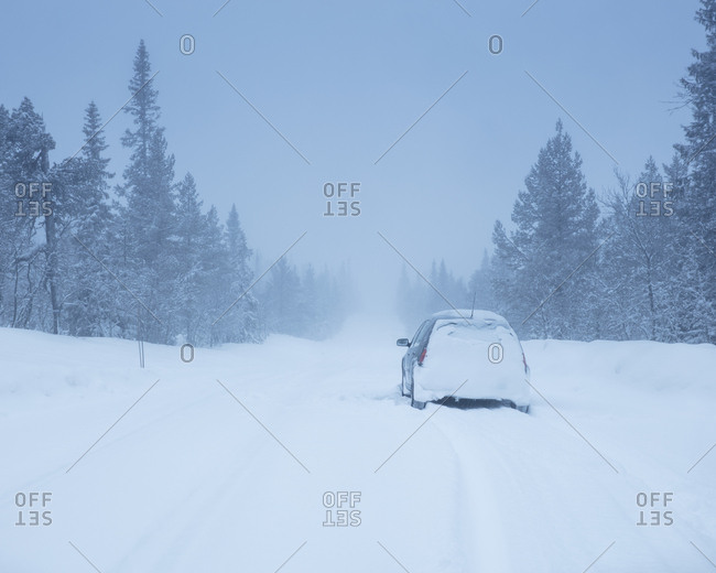 Car on rural road during winter in Dalarna, Sweden