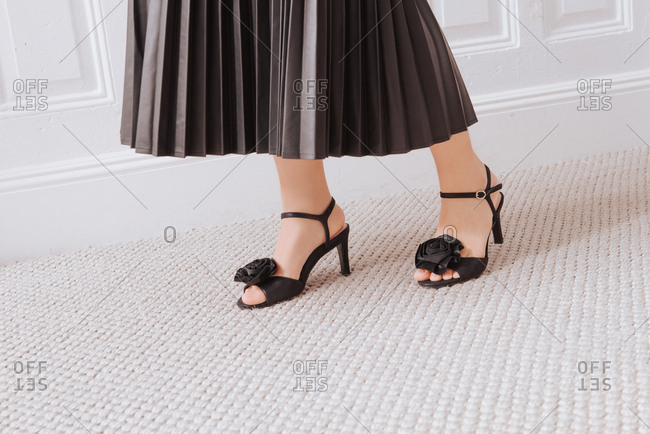 Woman in black pleated skirt and black heels