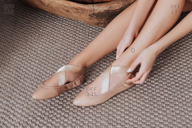 Legs of woman adjusting her ballet flats