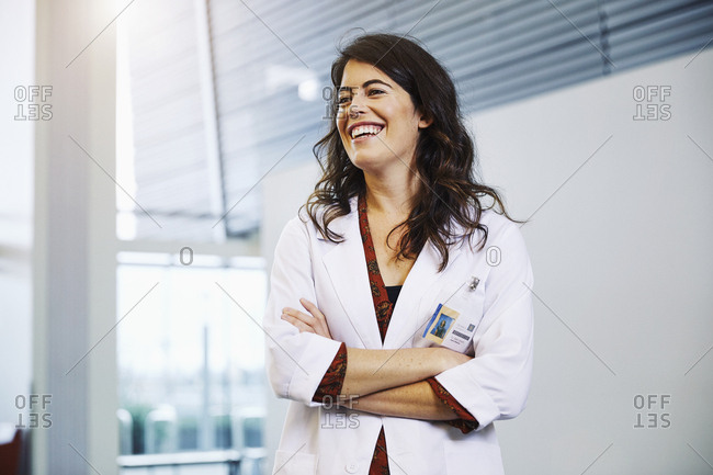 Happy female doctor looking away while standing arms crossed in hospital