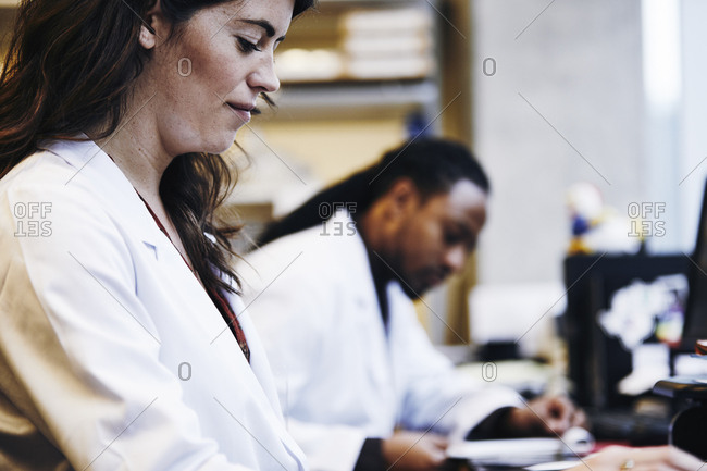 Side view of female medical researcher working by male colleague in laboratory