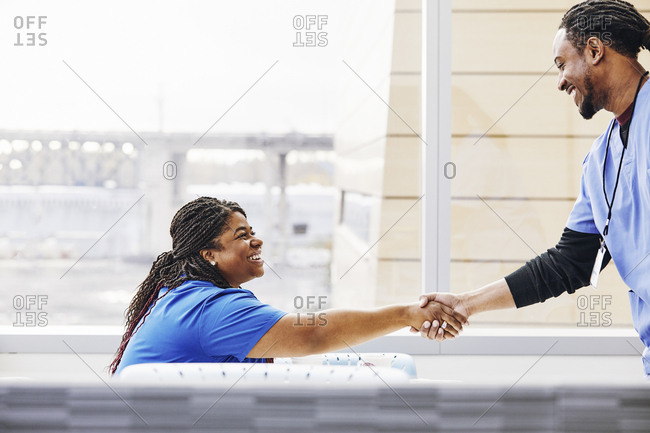 Smiling female nurse shaking hands with male colleague in hospital canteen