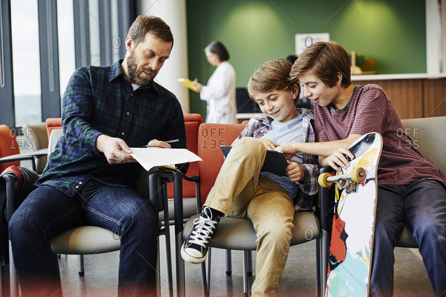 Father writing on paper while sitting with sons in waiting room at hospital
