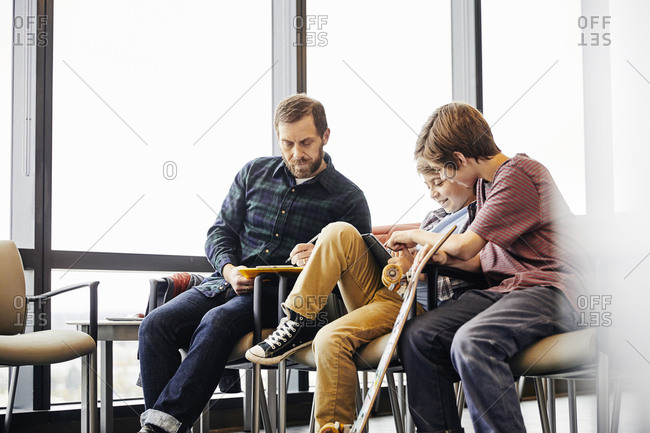 Man writing on clipboard while sons using digital tablet in waiting room at hospital