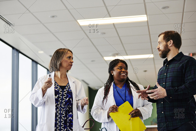 Middle aged man talking with female doctors while standing in hospital lobby