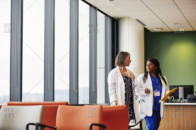 Female doctor discussing with colleague over documents by reception at hospital