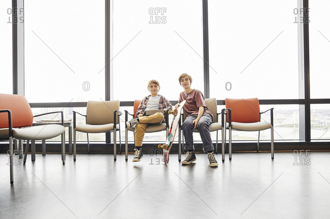 Portrait of smiling siblings with digital tablet and skateboard sitting on chairs in hospital waiting room
