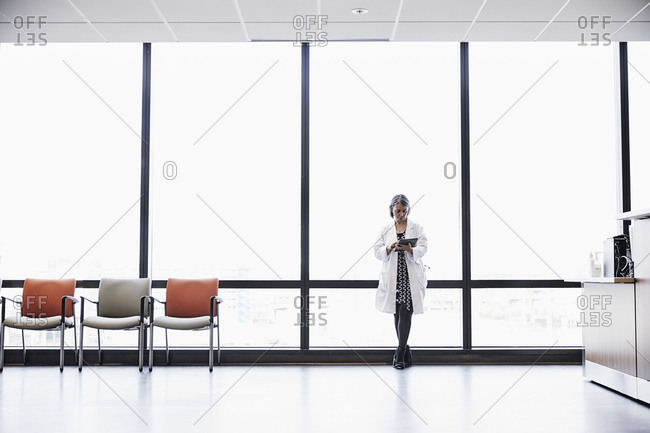 Mature female doctor using digital tablet while standing against window in hospital on sunny day