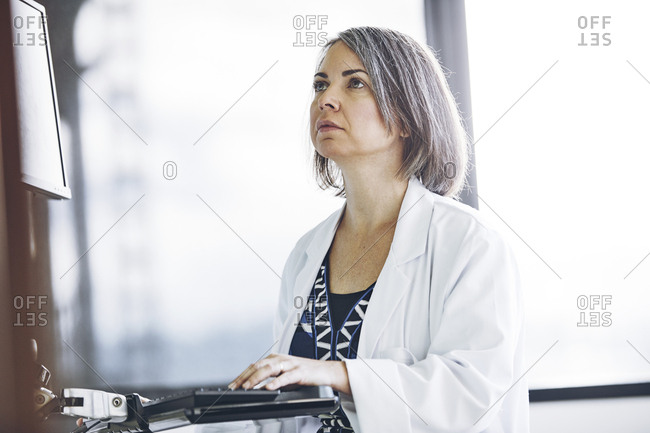 Confident serious female researcher using computer in hospital