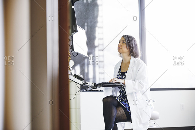 Confident female doctor using computer in hospital exam room