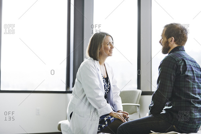 Smiling female doctor talking to male patient in exam room