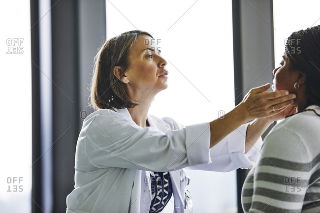 Mature female doctor examining glands in the neck of young patient at hospital
